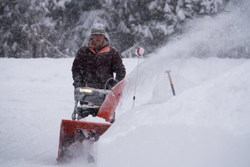 Το άτομο καθαρίζει Driveway κατά τη διάρκεια της χειμερινής θύελλας στοκ φωτογραφίες