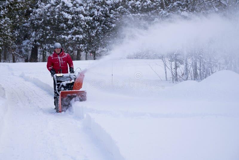 Το άτομο καθαρίζει Driveway κατά τη διάρκεια της χειμερινής θύελλας στοκ φωτογραφία