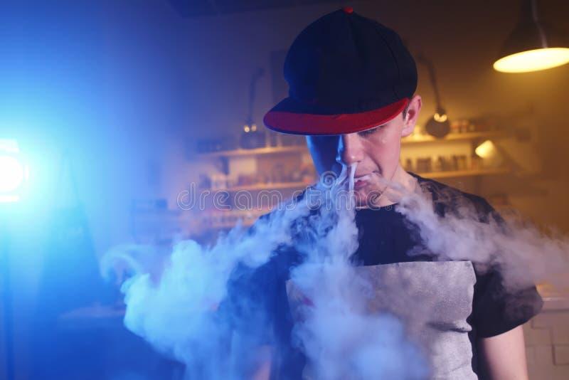 Το άτομο καπνίζει ένα ηλεκτρονικό τσιγάρο στο κατάστημα vape στοκ εικόνες με δικαίωμα ελεύθερης χρήσης