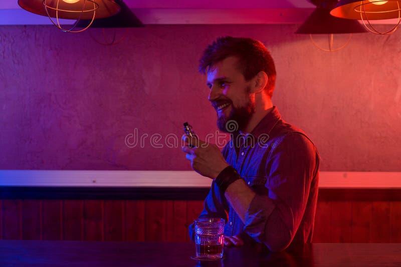 Το άτομο καπνίζει ένα ηλεκτρονικό τσιγάρο στο κατάστημα vape στοκ φωτογραφία με δικαίωμα ελεύθερης χρήσης