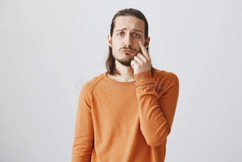 Το άτομο κινείται προς τα δάκρυα Εσωτερικός πυροβολισμός του ελκυστικού ενήλικου αρσενικού με τη γενειάδα που δείχνει στο βλέφαρο στοκ εικόνα με δικαίωμα ελεύθερης χρήσης