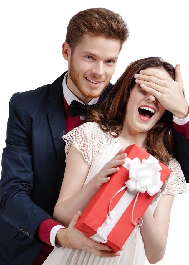 Το άτομο κλείνει τα μάτια της φίλης του που παρουσιάζει ένα δώρο στοκ φωτογραφία με δικαίωμα ελεύθερης χρήσης