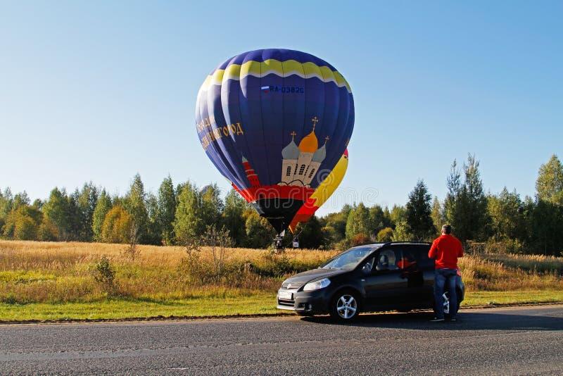 Το άτομο κοντά στην προσοχή αυτοκινήτων ως δύο μπαλόνια ζεστού αέρα προσγειώνεται στον τομέα στο φεστιβάλ της αεροναυτικής σε per στοκ εικόνα