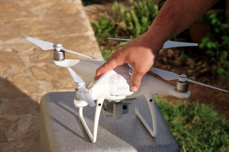 Το άτομο κρατά έναν κηφήνα διαθέσιμο και τη χρησιμοποίηση της νέας τεχνολογίας Άσπρα χέρια ατόμων κηφήνων και φωτογράφων τετραγών στοκ εικόνα με δικαίωμα ελεύθερης χρήσης