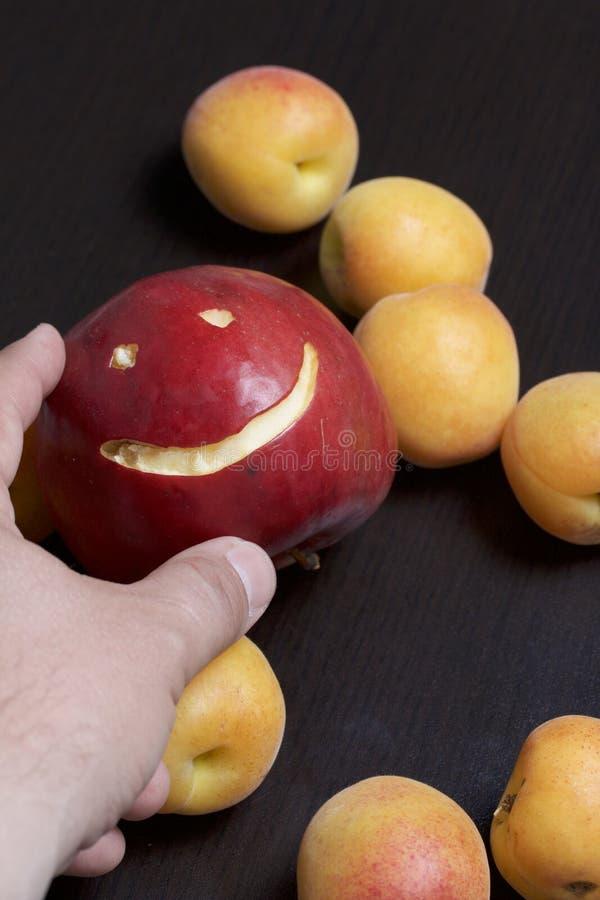Το άτομο κρατά ένα κόκκινο μήλο με χαρασμένη emoticon στο χέρι του Υπάρχει βερίκοκα στο υπόβαθρο στοκ εικόνες