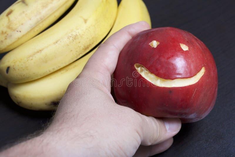 Το άτομο κρατά ένα κόκκινο μήλο με χαρασμένη emoticon στο χέρι του Υπάρχει μπανάνες στο υπόβαθρο στοκ φωτογραφία