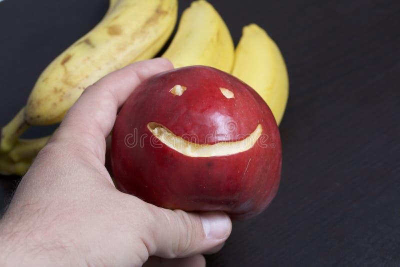 Το άτομο κρατά ένα κόκκινο μήλο με χαρασμένη emoticon στο χέρι του Υπάρχει μπανάνες στο υπόβαθρο στοκ φωτογραφίες