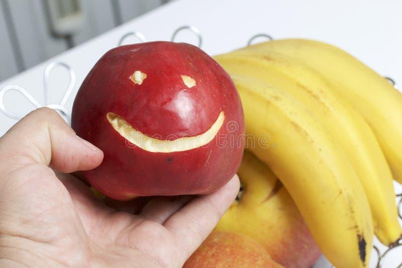 Το άτομο κρατά ένα κόκκινο μήλο με χαρασμένη emoticon στο χέρι του Υπάρχει ένα καλάθι φρούτων στο υπόβαθρο Διάφορα μήλα και β στοκ εικόνες