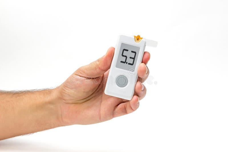 Το άτομο κρατά το διαθέσιμο επίπεδο ζάχαρης αίματος μέτρων glucometer χεριών στοκ φωτογραφία με δικαίωμα ελεύθερης χρήσης