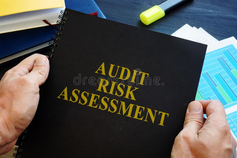 Το άτομο κρατά την έκθεση αξιολόγησης του κινδύνου λογιστικού ελέγχου στοκ φωτογραφίες με δικαίωμα ελεύθερης χρήσης