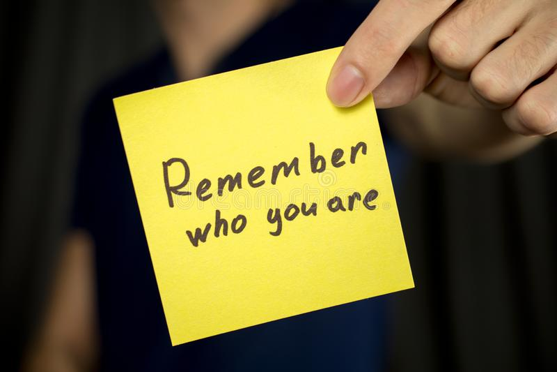 Το άτομο κρατά ότι η κίτρινη επιγραφή αυτοκόλλητων ετικεττών θυμάται ποιοι είστε στοκ φωτογραφία με δικαίωμα ελεύθερης χρήσης