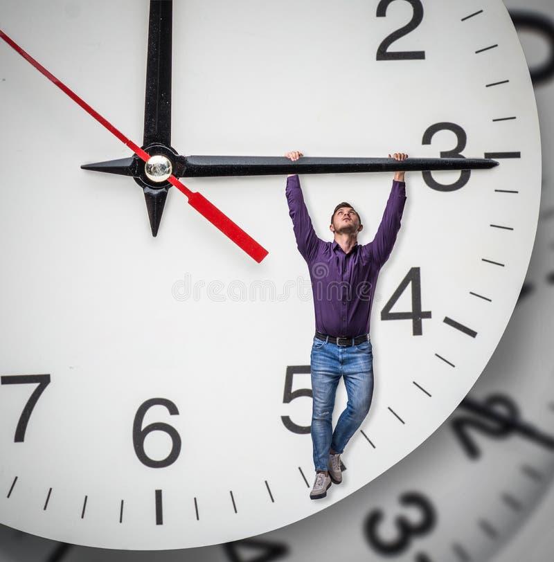 Το άτομο κρεμά στο βέλος ενός τεράστιου ρολογιού στοκ εικόνα με δικαίωμα ελεύθερης χρήσης