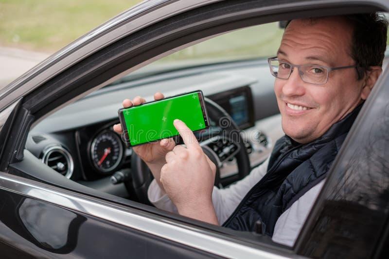 Το άτομο Μεσαίωνα παρουσιάζει smartphone με την οθόνη chromakey στοκ εικόνες