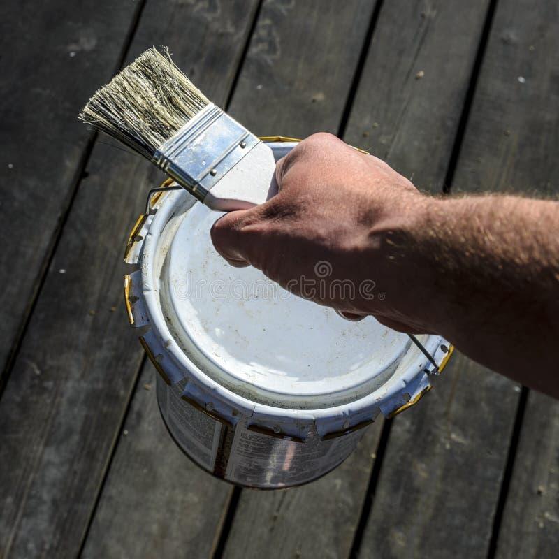 Το άτομο με ένα ισχυρό χέρι φέρνει ένα δοχείο του χρώματος πέρα από το πεζούλι και κρατά μια βούρτσα, επισκευή σε ένα ιδιωτικό σπ στοκ εικόνες