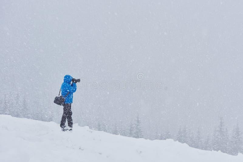 Το άτομο με το σακίδιο πλάτης πηγαίνει πέρα από το κωνοφόρο δάσος μετά από τη θύελλα χιονιού Πίσω άποψη, τονισμένη εικόνα στοκ φωτογραφία με δικαίωμα ελεύθερης χρήσης