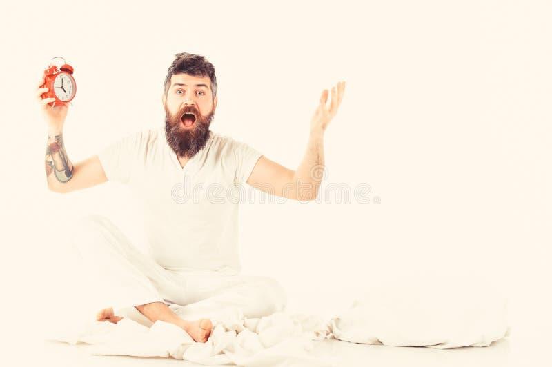 Το άτομο με το συγκλονισμένο πρόσωπο κάθεται κοντά στο μαξιλάρι, κρατά το ξυπνητήρι στοκ εικόνες