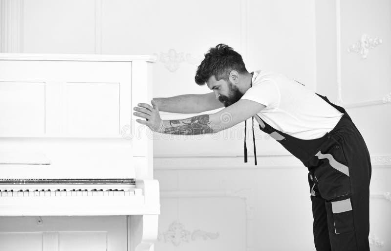 Το άτομο με τη γενειάδα και mustache, εργαζόμενος στις φόρμες ωθεί το πιάνο, το άσπρο υπόβαθρο Έννοια υπηρεσιών παράδοσης Κινήσει στοκ εικόνες