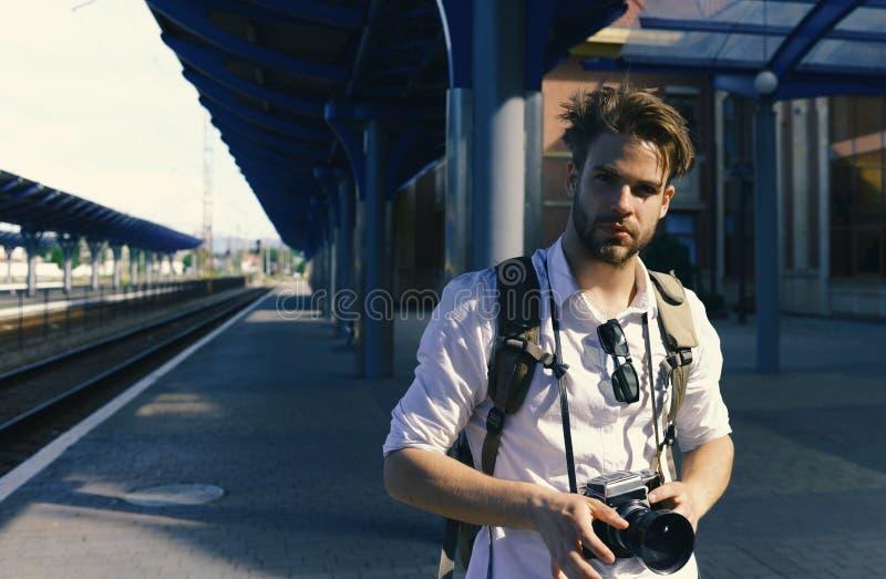 Το άτομο με τη γενειάδα κρατά το photocamera στο υπόβαθρο σταθμών Αστική φωτογραφία και διακινούμενη έννοια Τουρίστας έτοιμος να  στοκ φωτογραφίες