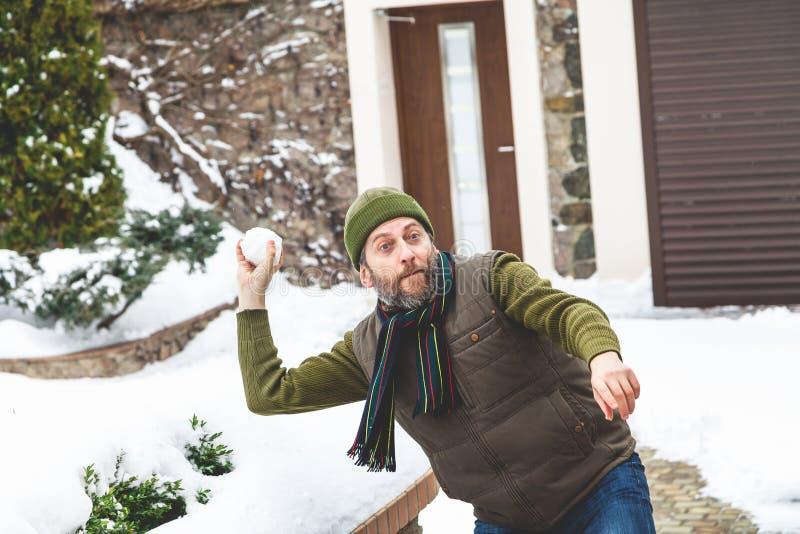 Το άτομο με τη γενειάδα στην ΚΑΠ του ρίχνει τις χιονιές στο ναυπηγείο στοκ εικόνες με δικαίωμα ελεύθερης χρήσης