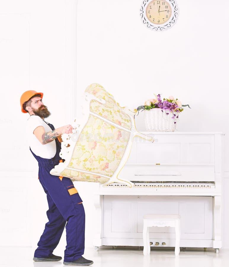 Το άτομο με τη γενειάδα, τον εργαζόμενο στις φόρμες και το κράνος ανυψώνει επάνω την πολυθρόνα, άσπρο υπόβαθρο Ο αγγελιαφόρος παρ στοκ εικόνα