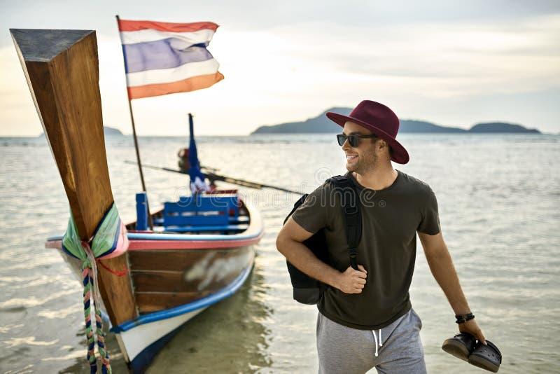 Το άτομο με τις καλαμιές στέκεται με τις σκοτεινές πτώσεις κτυπήματος στα ρηχά νερά κοντά στη βάρκα στοκ φωτογραφία με δικαίωμα ελεύθερης χρήσης