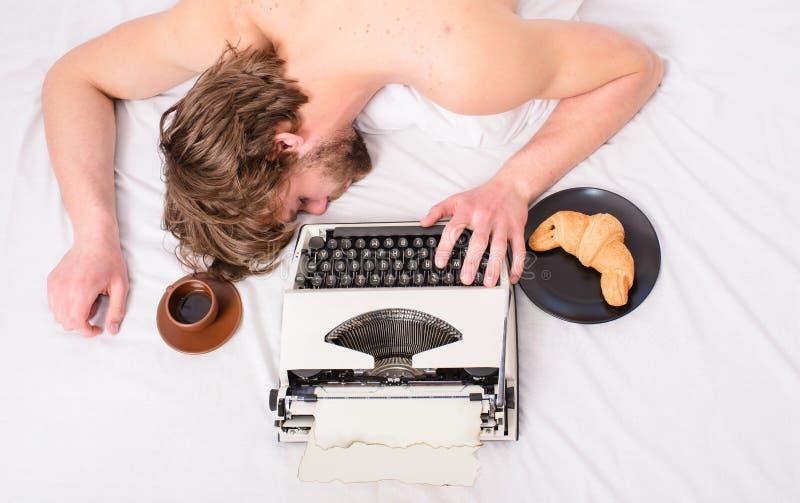 Το άτομο με τον καφέ γραφομηχανών βάζει το κρεβάτι Το άτομο νυσταλέο βάζει τα κλινοσκεπάσματα ενώ εργασία Ο συγγραφέας χρησιμοποί στοκ εικόνες με δικαίωμα ελεύθερης χρήσης