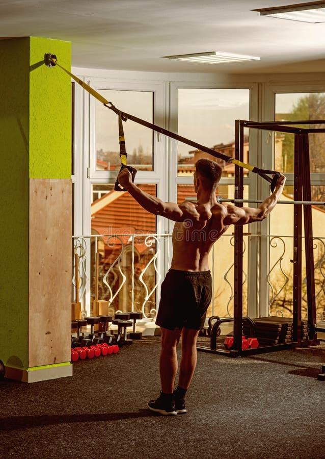 Το άτομο με το nude κορμό, και μυϊκός πίσω στη γυμναστική απολαμβάνει, trx Άτομο με το κορμό, αθλητικός τύπος, αθλητής, μυϊκός φα στοκ εικόνες