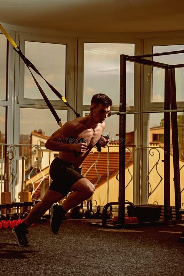 Το άτομο με το nude κορμό, και το μυϊκό στήθος στη γυμναστική απολαμβάνουν, trx Ο αθλητικός τύπος, αθλητής, μυϊκός φαλλοκράτης ασ στοκ εικόνες