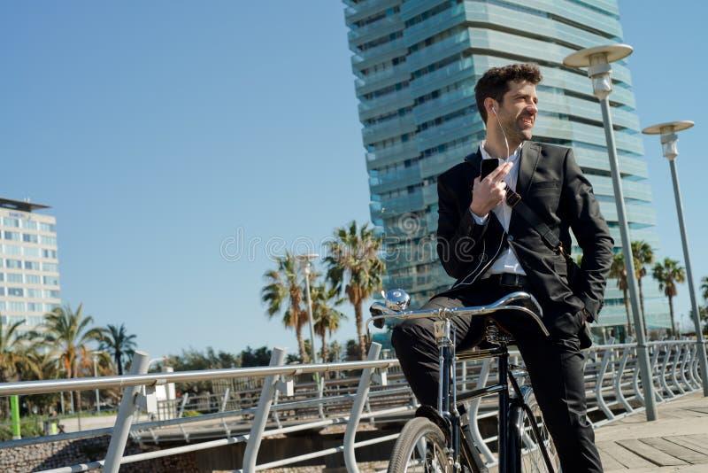 Το άτομο μιλά για το τηλέφωνο με τα ακουστικά στο ποδήλατο στοκ εικόνα