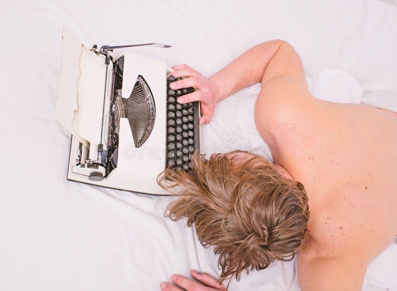 Το άτομο νυσταλέο βάζει τα κλινοσκεπάσματα ενώ εργασία Ο συγγραφέας χρησιμοποίησε την ντεμοντέ γραφομηχανή Εξαντλώντας επάγγελμα  στοκ εικόνα με δικαίωμα ελεύθερης χρήσης