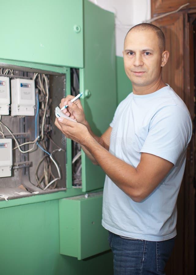 Το άτομο ξαναγράφει τις αναγνώσεις μετρητών ηλεκτρικής δύναμης στοκ φωτογραφίες