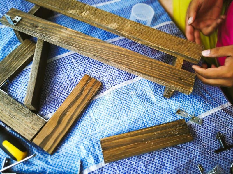 Το άτομο ξυλουργών τακτοποιεί την ξύλινη σανίδα στοκ φωτογραφία