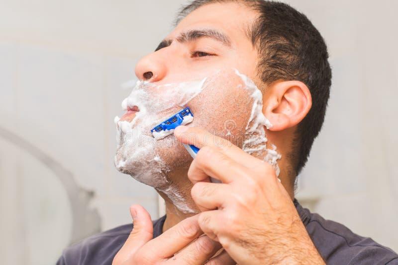 Το άτομο ξυρίζει τη γενειάδα του με ένα ξυράφι στοκ εικόνες