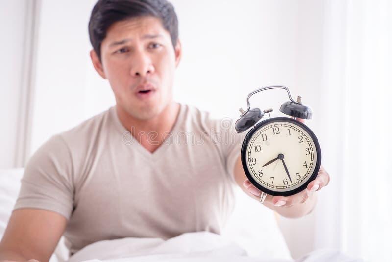Το άτομο ξύπνησε αργά και παρουσιάζει ξυπνητήρι στη κάμερα στοκ φωτογραφίες με δικαίωμα ελεύθερης χρήσης