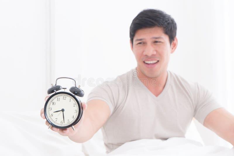 Το άτομο ξύπνησε αργά και παρουσιάζει ξυπνητήρι στη κάμερα στοκ φωτογραφία με δικαίωμα ελεύθερης χρήσης