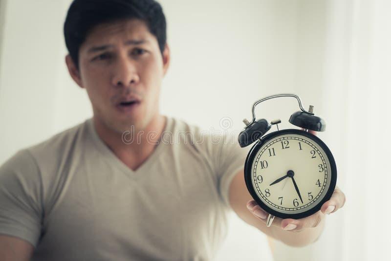 Το άτομο ξύπνησε αργά και παρουσιάζει ξυπνητήρι στη κάμερα στοκ εικόνα με δικαίωμα ελεύθερης χρήσης