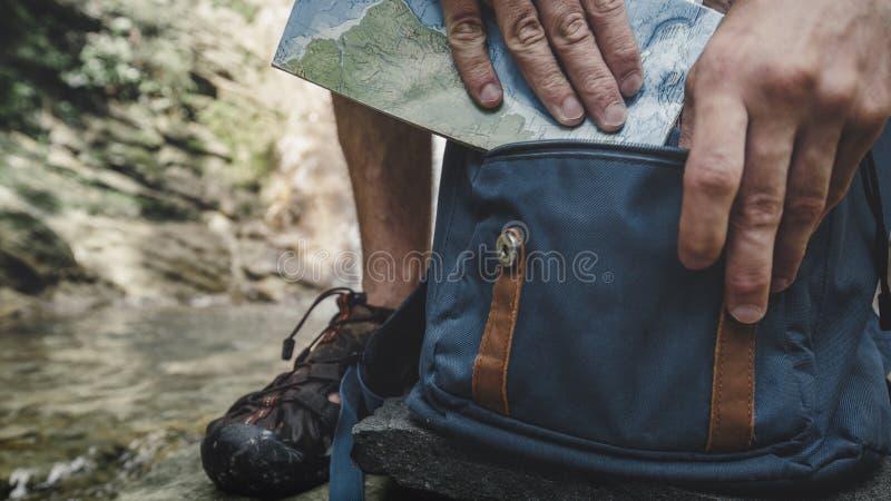Το άτομο οδοιπόρων βάζει το χάρτη ταξιδιού στο σακίδιο πλάτης ερευνώντας την έννοια πεζοπορίας περιπέτειας στοκ εικόνες
