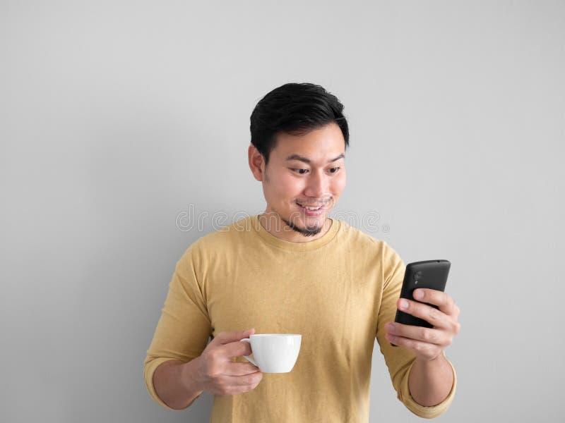 Το άτομο πίνει τον καφέ και το smartphone χρήσης στοκ εικόνα με δικαίωμα ελεύθερης χρήσης