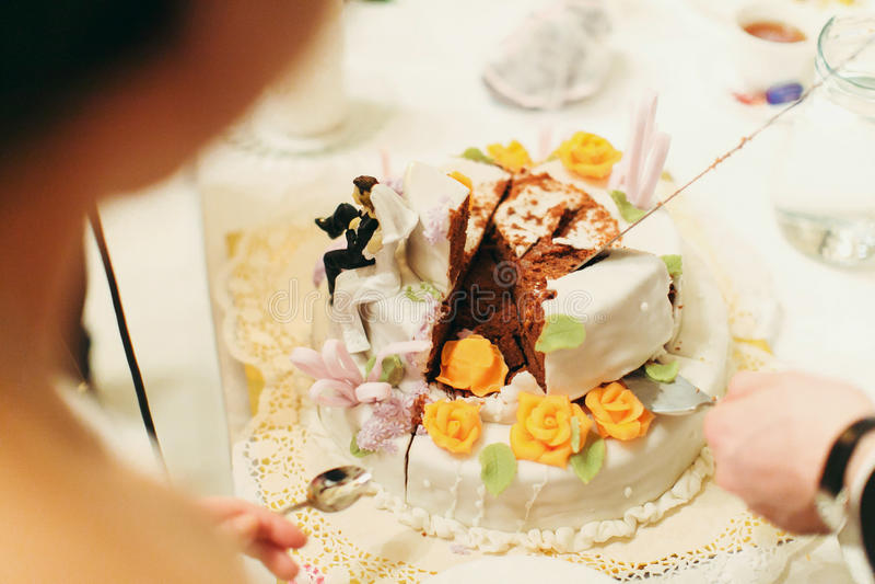 Το άτομο παίρνει ένα κομμάτι του γαμήλιου κέικ ενώ η νύφη στέκεται με ένα spoo στοκ φωτογραφίες με δικαίωμα ελεύθερης χρήσης