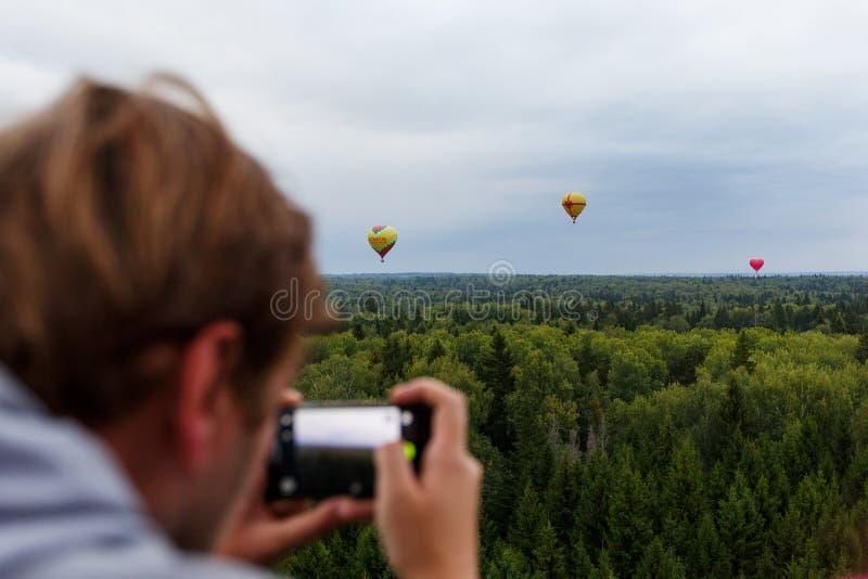 Το άτομο παίρνει μια εικόνα με κινητό του των μπαλονιών ζεστού αέρα στοκ εικόνες
