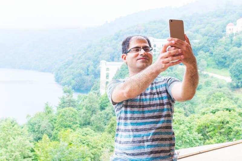 Το άτομο παίρνει μια εικόνα του στο τηλέφωνο ενάντια στο βουνό στοκ εικόνα