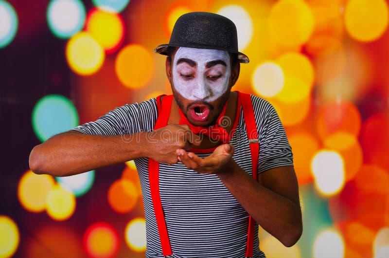 Το άτομο παντομίματος που φορά την του προσώπου τοποθέτηση χρωμάτων για τη κάμερα, χρησιμοποίηση δίνει την αλληλεπιδρώντας γλώσσα στοκ εικόνες