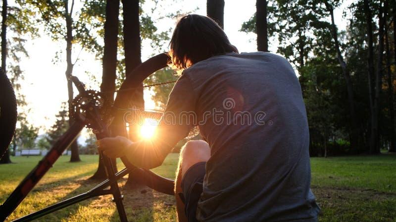 Το άτομο περιστρέφει και επισκευάζει μια ρόδα σε ένα ποδήλατο, οι επισκευές τύπων ένα ποδήλατο στο ηλιοβασίλεμα στο πάρκο στοκ φωτογραφίες
