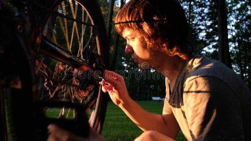 Το άτομο περιστρέφεται μια ρόδα σε ένα ποδήλατο, οι επισκευές τύπων τα spokes στο ηλιοβασίλεμα στο πάρκο στοκ εικόνα