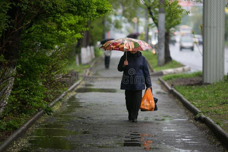 Το άτομο πηγαίνει κάτω από μια ομπρέλα στη βροχή στοκ φωτογραφία με δικαίωμα ελεύθερης χρήσης