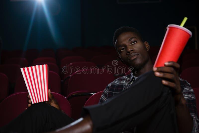Το άτομο που έχουν popcorn και το κρύο πίνουν προσέχοντας τον κινηματογράφο στοκ εικόνες με δικαίωμα ελεύθερης χρήσης