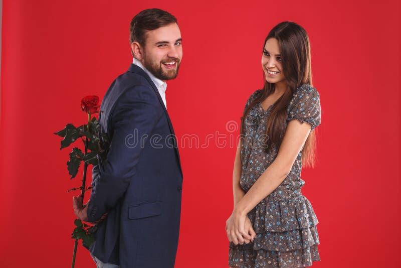 Το άτομο που εκπλήσσει τη χαριτωμένη φίλη του με το κόκκινο αυξήθηκε κατά τη ρομαντική ημερομηνία στοκ φωτογραφία