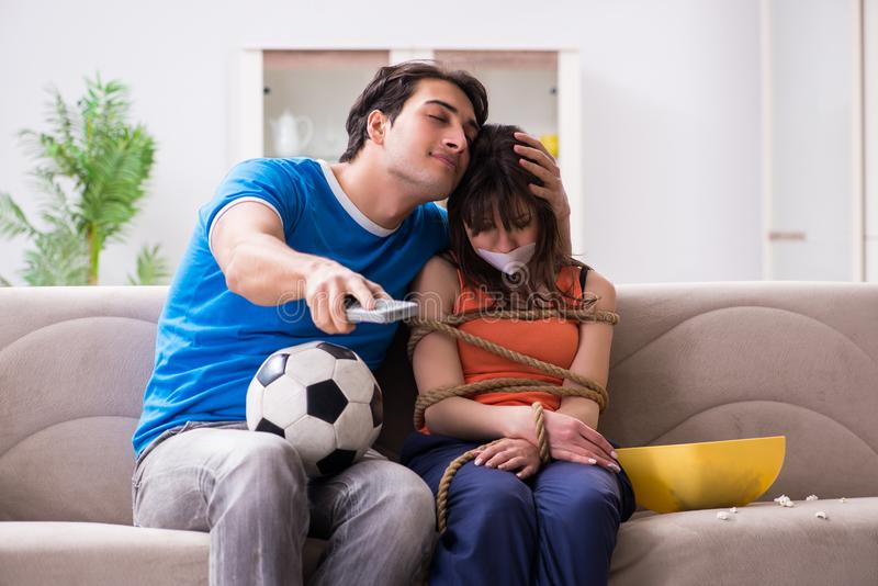 Το άτομο που εμπλέκει τη σύζυγό του για να προσέξει το αθλητικό ποδόσφαιρο στοκ εικόνες