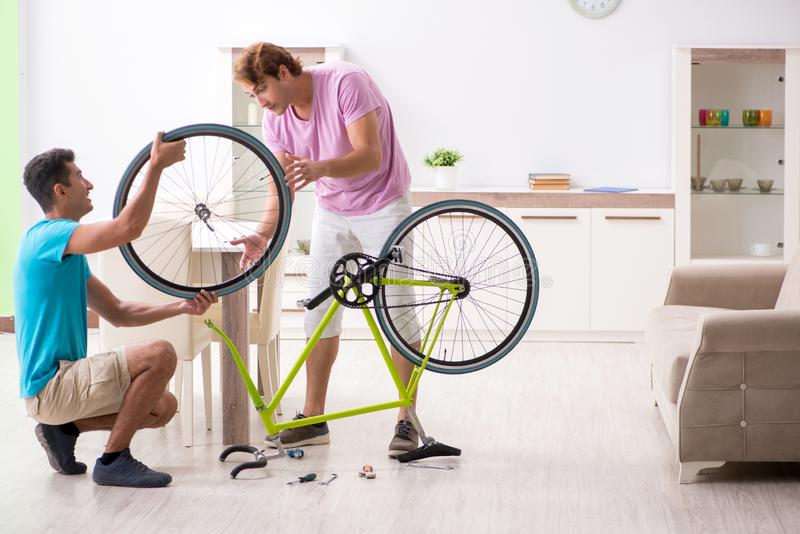 Το άτομο που επισκευάζει το σπασμένο ποδήλατό του στοκ εικόνα