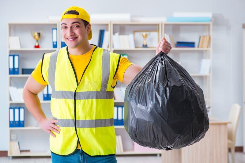 Το άτομο που καθαρίζει το γραφείο και που κρατά την τσάντα απορριμάτων στοκ εικόνες με δικαίωμα ελεύθερης χρήσης